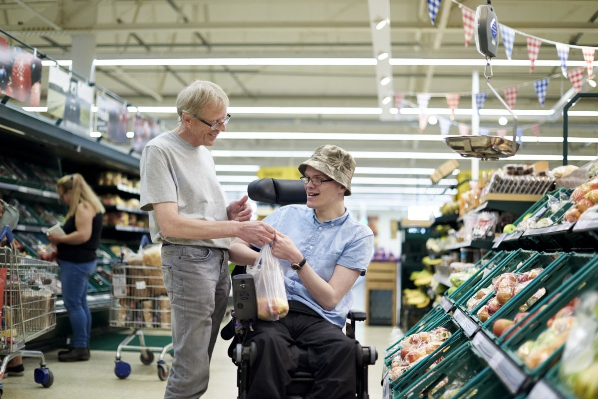 Support worker Chris helping client James shopping in a supermarket