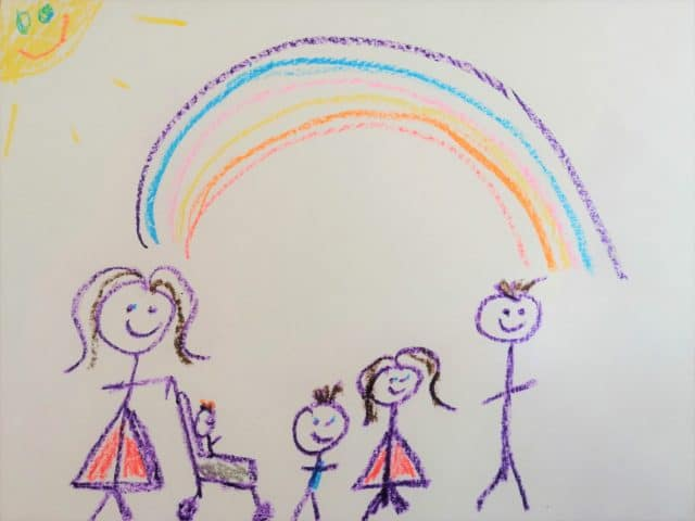 Lizzy and her children drawn in crayon by on of her children standing below a rainbow