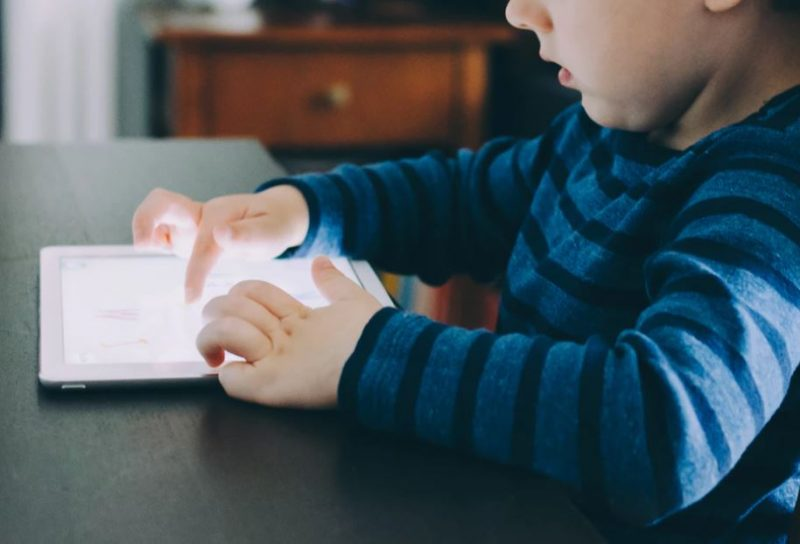 Young boy learning to use an iPad