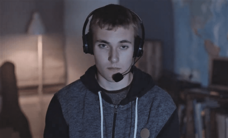 A teenage boy playing an online video game while wearing a headset
