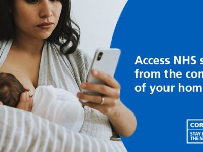 An NHS Health at Home poster. A woman holding a baby while checking her mobile phone.