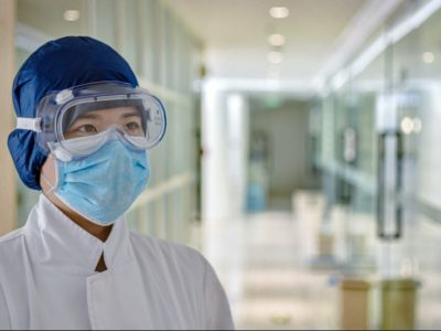 A doctor wearing a surgical mask, goggles and protective headgear