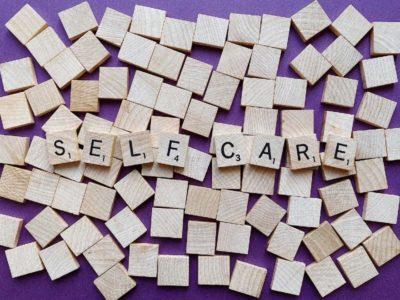"Scrabble tiles spelling out ""self care"""""