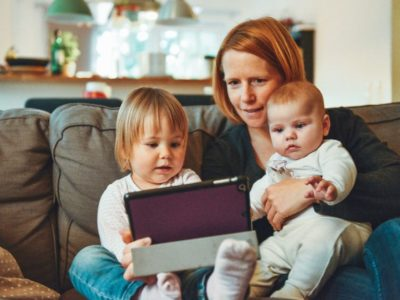 a mother and two children looking at an iPad