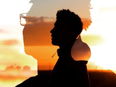 a silhouette of a man's head against a sunset