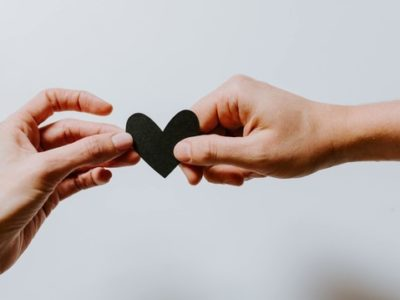 two hands passing a paper heart