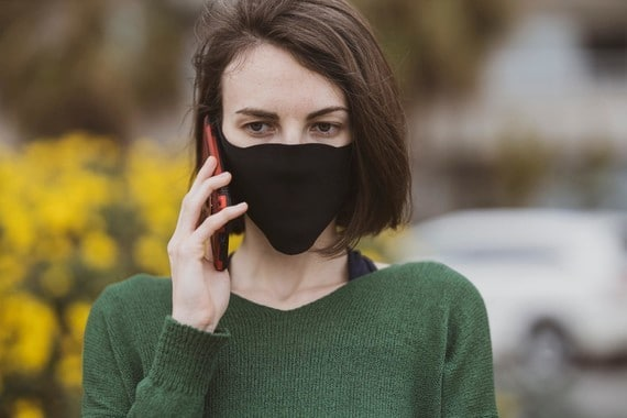 a woman wearing a face mask using a mobile phone