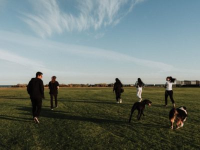 a group of young people walking across a field