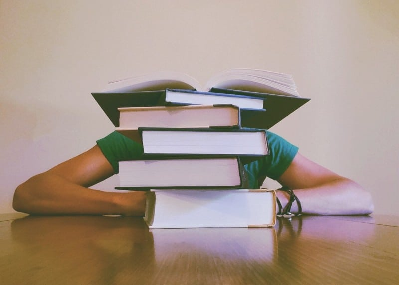 a person hidden behind a stack of books