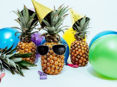 three pineapples surrounded by balloons