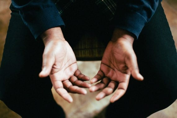 a person opening their hands upward in prayer