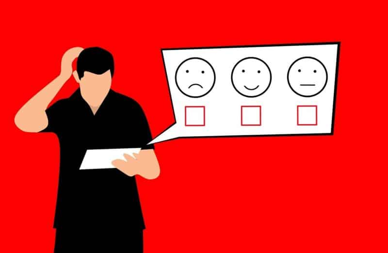 an illustration of a person looking at a survey with three options denoted by a sad face, a happy face and a neutral face