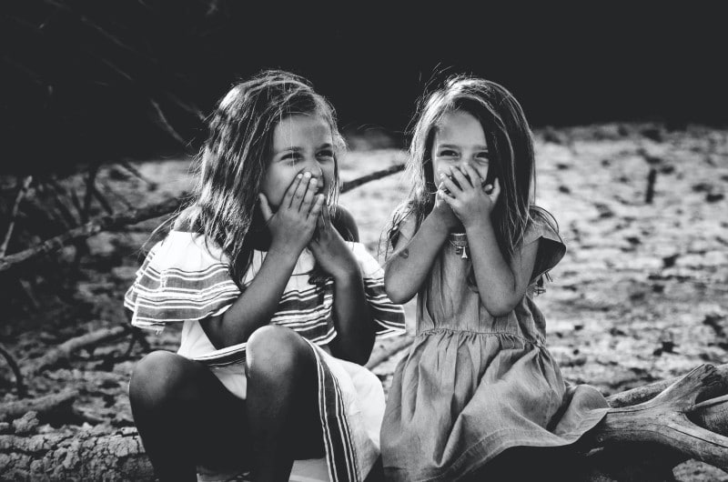 two sisters sat on a log smiling behind their hands