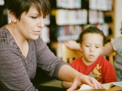a women reading a book with a child