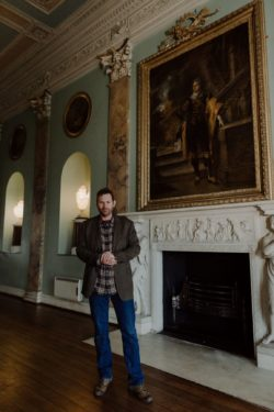 The 19th Earl of Devon standing next to a fireplace in Powderham castle