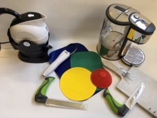 A range of kitchen accessories including a kettle, easy hold knives, dycem mat