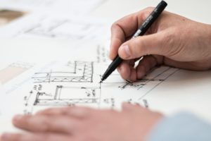 An image of hands that are holding a pen going over architecture plans