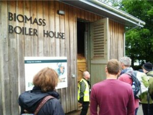 People listening to a talk outside the biomass boiler house