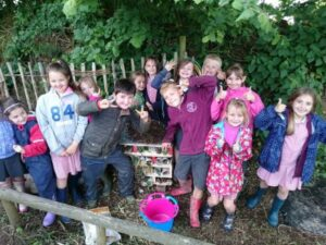 School children smiling with a new bug hotel