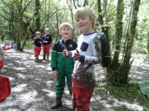 Two school children smiling at the camera covered in mud