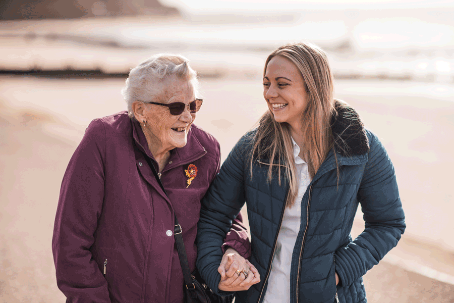 Care worker and client walking along the beach