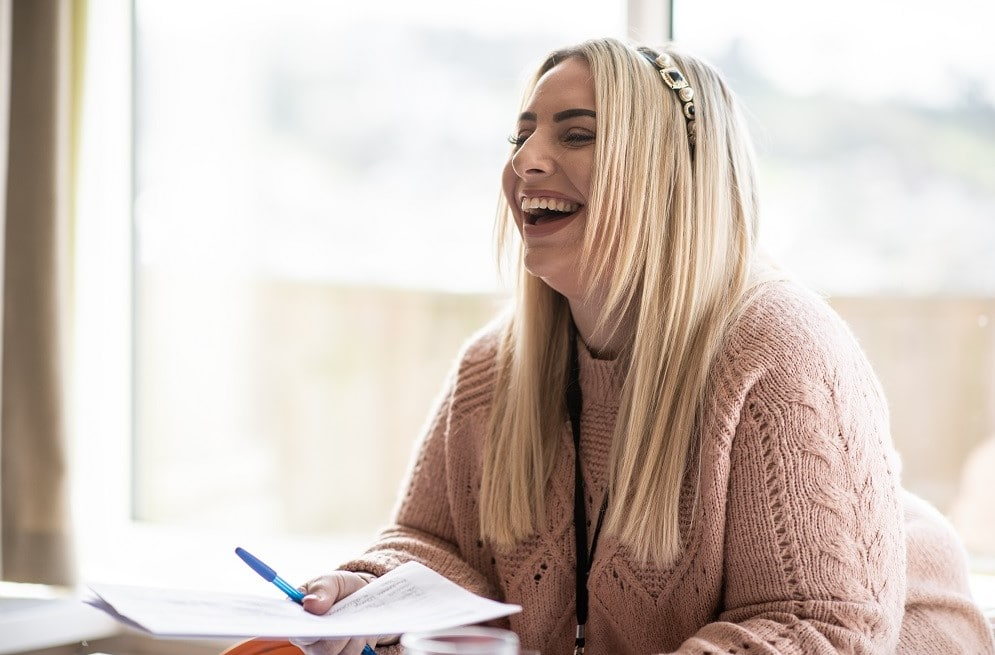 Multi-site registered manager, Lou, sat at a table holding some paper and laughing